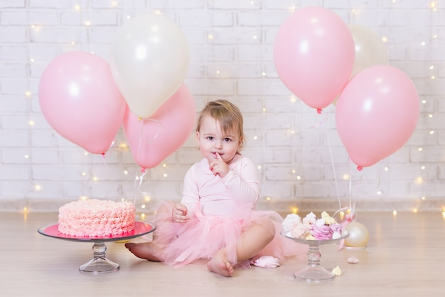 Primo compleanno bambina carina che mangia torta su sfondo muro di mattoni con luci e palloncini