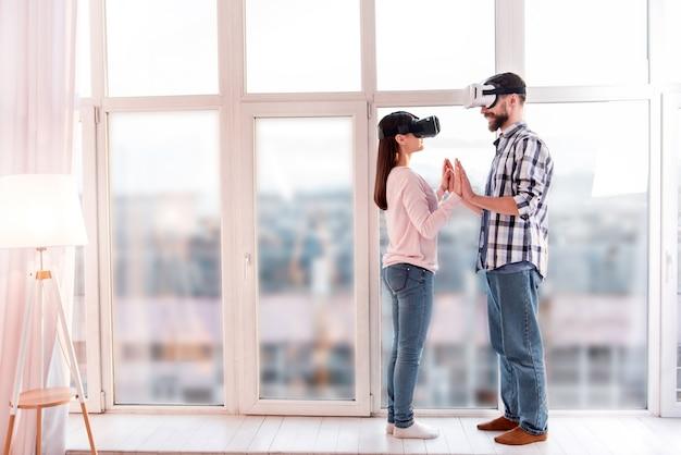 Primo ballo. integrale della dolce coppia soddisfatta innocente in posa vicino alla finestra mentre provano gli occhiali vr e si toccano le mani