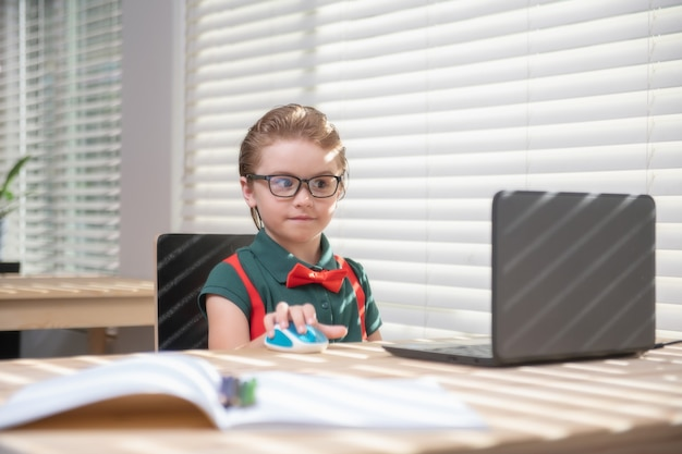 Primo giorno a scuola. simpatico bambino che utilizza il computer portatile, studiando il computer.