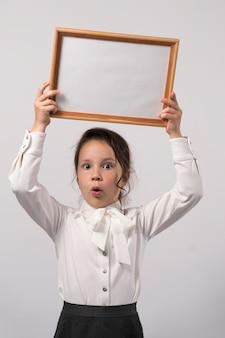 La ragazza della scuola elementare tiene un foglio bianco per l'iscrizione