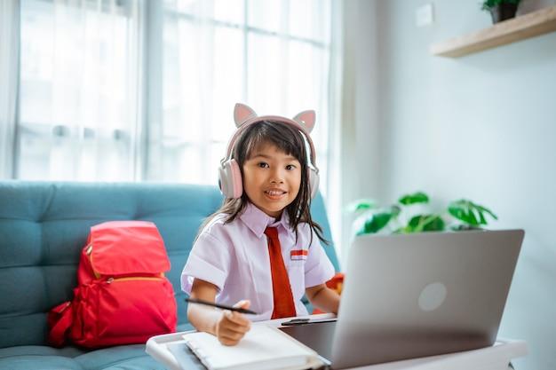 Studente di prima elementare con uniforme durante lo studio in classe online con l'insegnante a casa