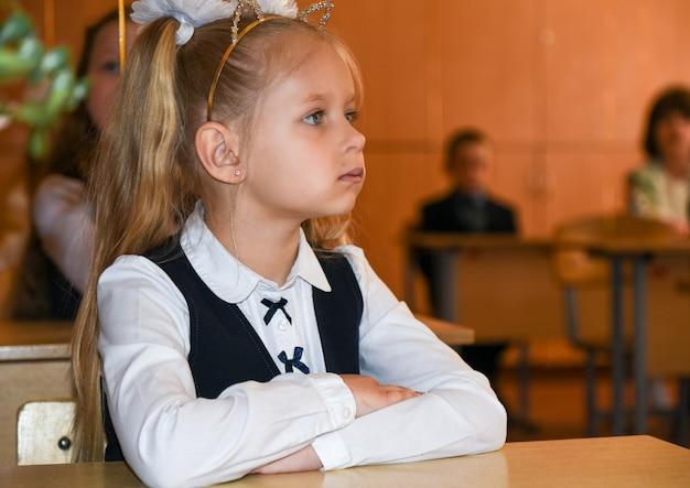 La ragazza della prima elementare si siede alla sua scrivania a scuola.