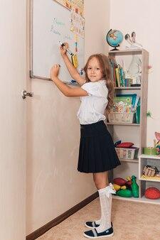 Un bambino di prima elementare sta alla lavagna e risolve un esempio