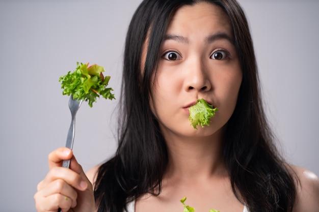 Donna asiatica di prima impressione che mangia insalata isolata sopra la parete bianca. stile di vita sano con il concetto di cibo pulito.