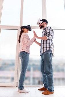Primo tentativo. basso angolo di giovani coppie piacevoli positive che si prendono per mano mentre si usano gli occhiali vr e in piedi vicino alla finestra