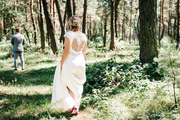 Primo incontro di nozze in giardino. l'incontro è di sposini su un campo verde all'aperto. la sposa torna dallo sposo, sorpresa nella natura. felice giorno del matrimonio. cerimonia di nozze nella foresta.