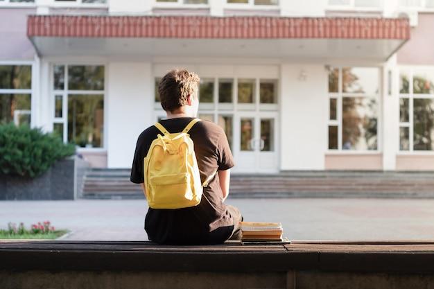 Studente del primo anno seduto fuori da un'università o da una struttura scolastica. matricola in attesa dell'inizio delle lezioni