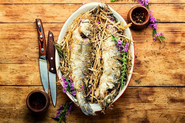 Pesce al forno con erbe e fieno di prato. branzino arrosto con erbe aromatiche