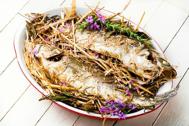 Pesce al forno con erbe e fieno di prato. branzino arrosto