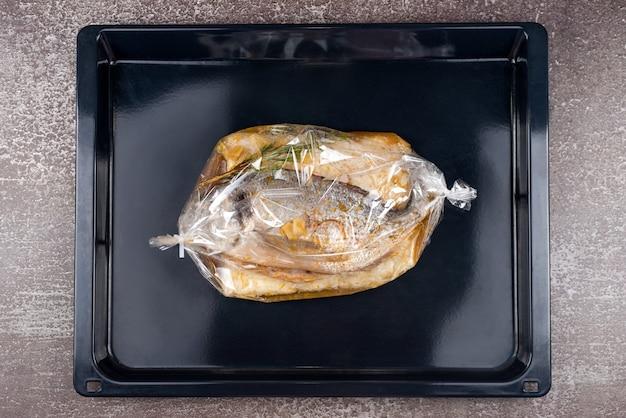 Pesce in borsa da forno. pesce dorado con riso, salsa ed erbe aromatiche avvolto in una teglia in forno pronto per la cottura. cucina mediterranea, piatto europeo.