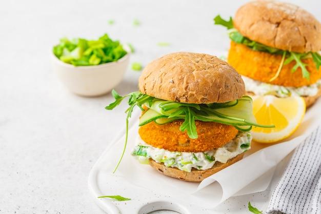 Hamburger di pesce con salsa di cetriolo, rucola e maionese, superficie bianca,