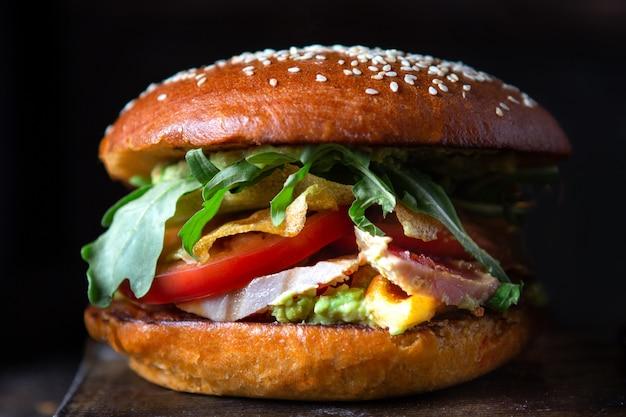 Hamburger di pesce con tonno fresco, salsa guacamole e rucola su sfondo scuro