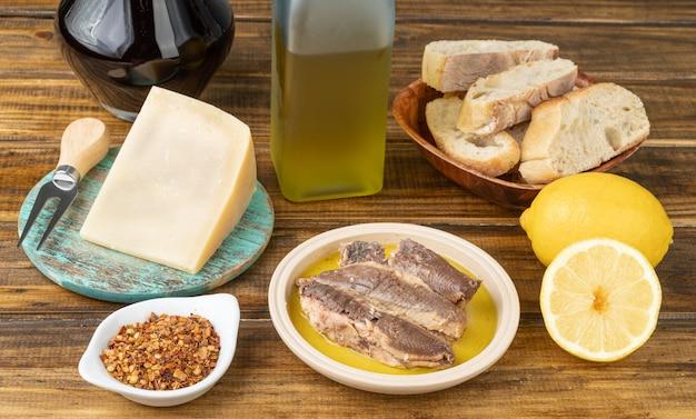 Pesce, formaggio, olio d'oliva, limone siciliano, vino, pepe e pane su un tavolo di legno. cibo mediterraneo.