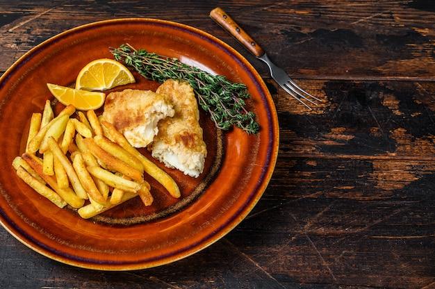 Fast food britannico di pesce e patatine fritte con patatine fritte e salsa tartara su un piatto rustico. fondo in legno scuro. vista dall'alto. copia spazio.