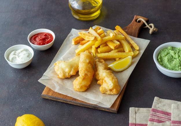 Pesce e patatine fritte su una superficie scura. fast food britannico. ricette. snack alla birra. cucina britannica tradizionale.
