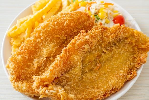 Pesce e patatine con mini insalata su piatto bianco