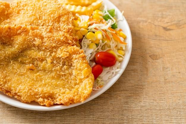 Fish and chips con mini insalata su piatto bianco