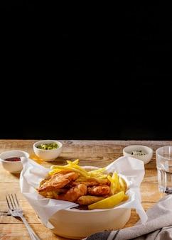 Pesce e patatine fritte con salse e copia spazio