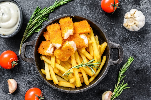Pesce e patatine fritte con salsa tartara sul tavolo nero.