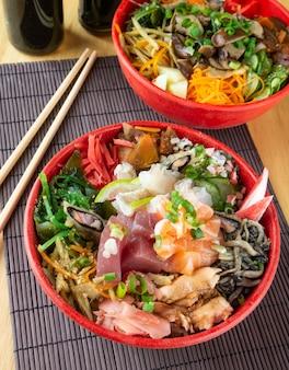 Chirashi di pesce, cibo giapponese su ciotole con hashi di legno.