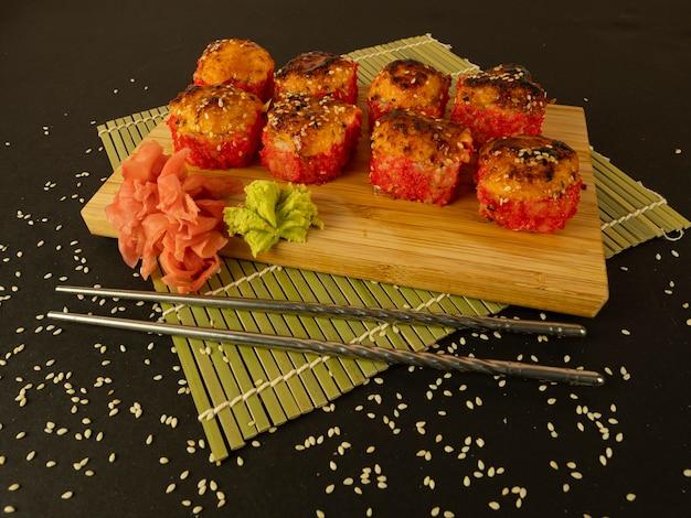 Involtini di pesce e cetriolo in caviale rosso, su una tavola di legno, su sfondo nero e cosparsi di semi di sesamo