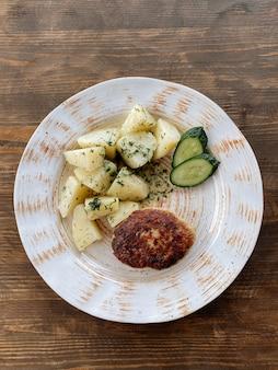Cotoletta di pesce con patate e verdure. cotoletta di luccio con erbe e verdure vista dall'alto