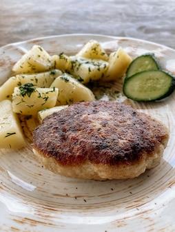 Cotoletta di pesce con patate e verdure. cotoletta di luccio con erbe e verdure