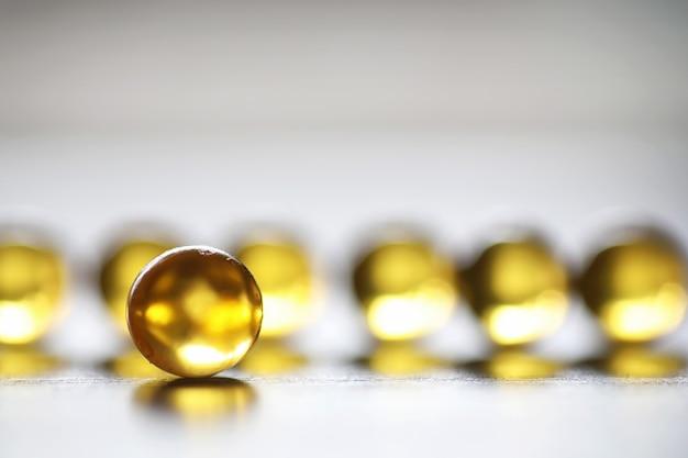 Grasso di pesce. prodotti medici per il trattamento delle malattie. il concetto di dipendenza sanitaria da compresse. capsule di olio di pesce su fondo di legno.