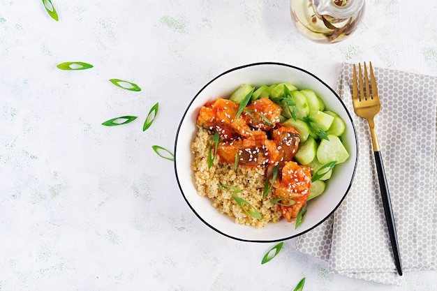 Filetto di pesce cotto in salsa di pomodoro con bulgur e cetriolo su un piatto su sfondo chiaro. concetto di mangiare sano. cucinare facilmente. vista dall'alto, piatto laico, copia dello spazio