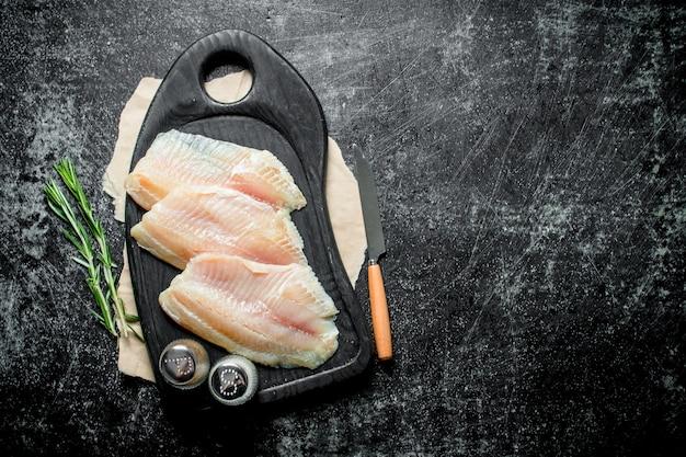 Filetto di pesce su un tagliere con un coltello, spezie e rosmarino.