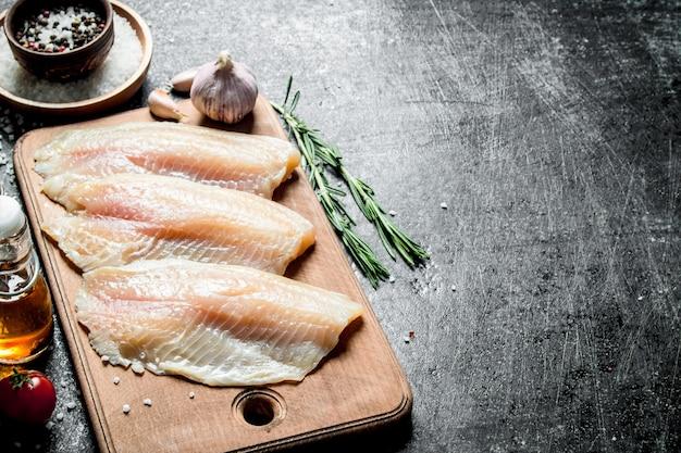 Filetto di pesce su un tagliere con rosmarino, aglio e spezie in una ciotola. sul nero rustico