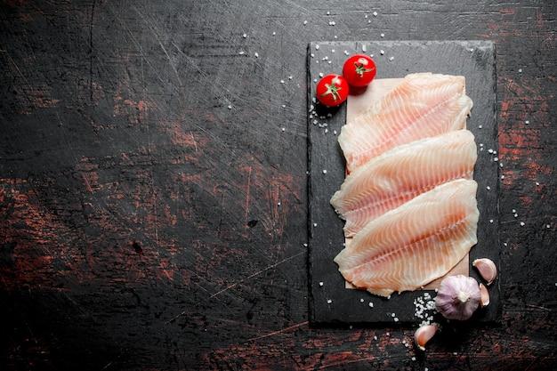 Filetto di pesce su carta su una tavola di pietra con aglio e pomodori. su fondo rustico scuro