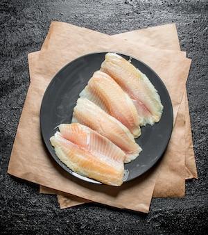 Filetto di pesce sulla zolla con carta sulla tavola rustica nera