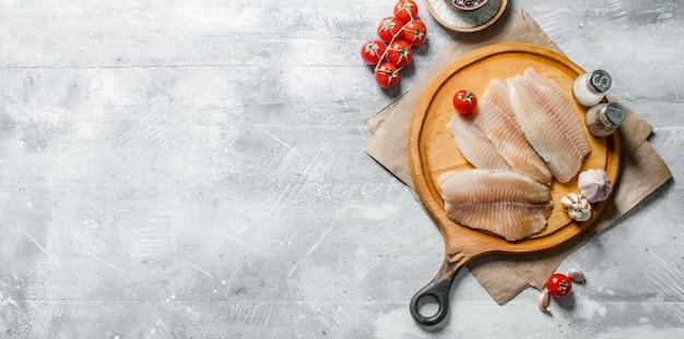 Filetto di pesce su un tagliere rotondo con spezie, pomodori e aglio.