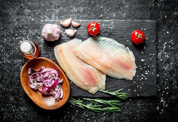 Filetto di pesce con cipolla tritata in una terrina, aglio e rosmarino. sul nero rustico