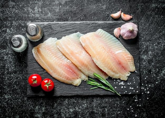 Filetto di pesce con aglio, spezie e pomodori.