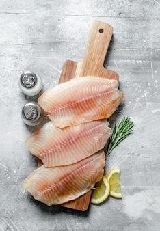 Filetto di pesce su un tagliere di legno con rosmarino, spezie e fette di limone. sulla superficie rustica bianca