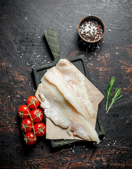 Filetti di pesce sulla carta con un coltello, rosmarino e spezie in una ciotola. su rustico scuro