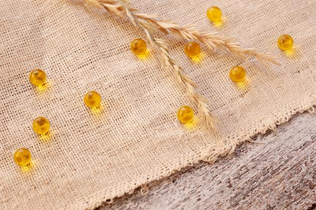 Pesce o olio di semi di lino in capsule o compresse, vitamine, omega su un tavolo di legno.
