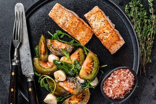 Farina di pesce con bistecche di filetto di salmone arrosto e insalata di pomodori rucola su un piatto. sfondo nero. vista dall'alto.