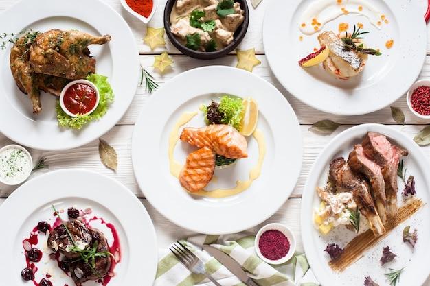 Piatto di varietà di piatti di carne e pesce. vista dall'alto sul buffet con assortimento di cibi sani e sostanziosi