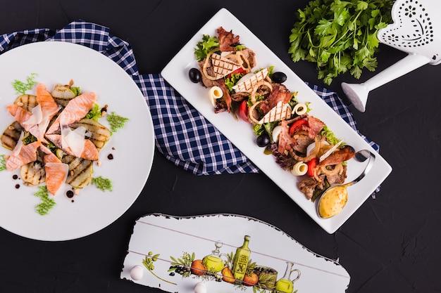 Pesce e carne affettati su un piatto bianco su una superficie nera (vista dall'alto) con un decoro