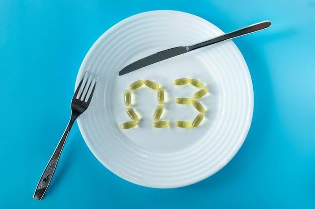 Le capsule di olio di pesce sono su un piatto bianco in forma di omega-3. servire con coltello e forchetta.