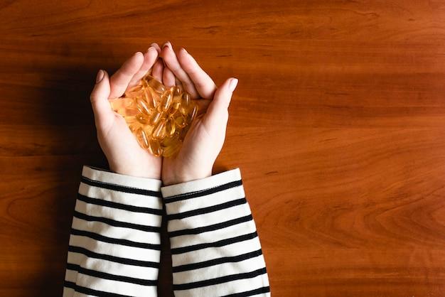 Capsule di olio di pesce sulle mani femminili