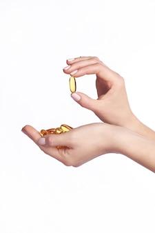 Capsule di olio di pesce omega 3 nelle mani.