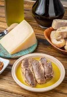 Pesce, olio d'oliva, parmigiano, pane e vino su un tavolo di legno. cucina mediterranea