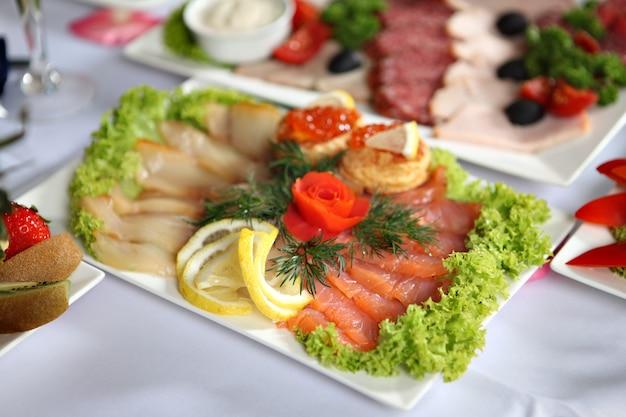 Piatto di pesce con pesce salato assortito, in piedi sul tavolo da pranzo decorato, accanto agli altri snack