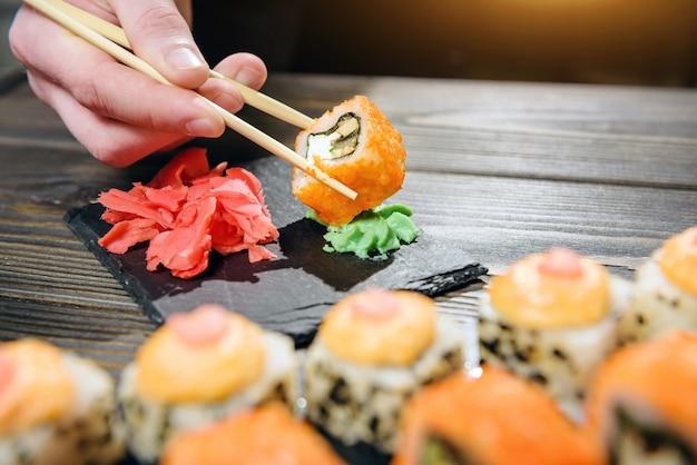 Rotolo di pesce tenuto con il primo piano delle bacchette. roll hiccup in wasabi.
