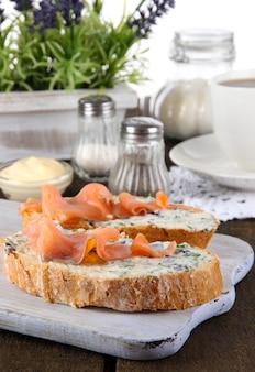 Panini di pesce e tazza di tè sul tagliere sulla tavola di legno