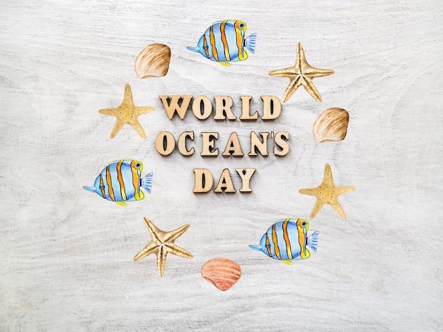 Pesce e conchiglie di forma rotonda con testo della giornata mondiale degli oceani su sfondo di legno chiaro
